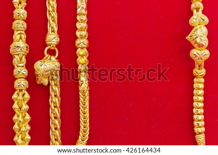 Luxury gold bracelets on red flannel,with copy space, gold ornament, gold bar, gold accessory, gold accessories, gold bracelet, gold necklace, gold asian, gold shop, gold background, gold pendant. - stock photo