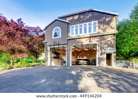 Luxury gray house with white trim and two motor boats in garage. Spacious driveway with concrete floor.