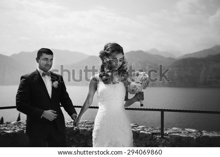 luxury happy couple on the background amazing landscape of the blue sea high mountains