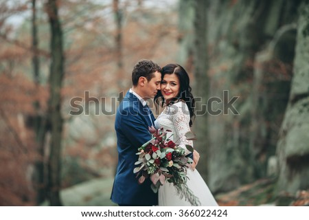 Luxury happy wedding couple kissing and embracing in forest with rocks - stock photo