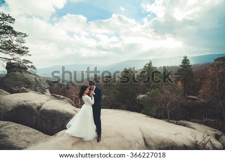 Luxury happy wedding couple kissing and embracing on the mountain with incredible landscape - stock photo