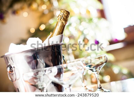 Luxury holiday composition, a bottle of chilled champagne in an ice bucket and vintage glasses, festive lights in the background - stock photo