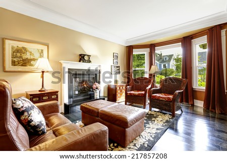 Luxury home interior in brown tones with fireplace, antique chairs, leather couch and ottoman - stock photo