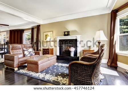 Luxury home interior in brown tones with fireplace, antique chairs, leather couch and ottoman