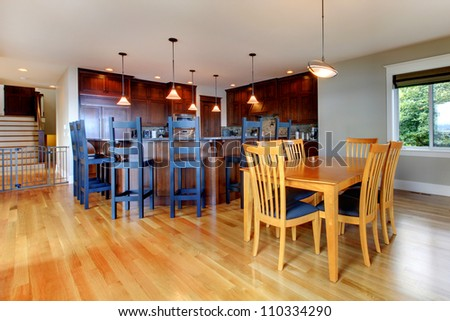 Luxury home kitchen and dining room with open floor plan and rich wood.