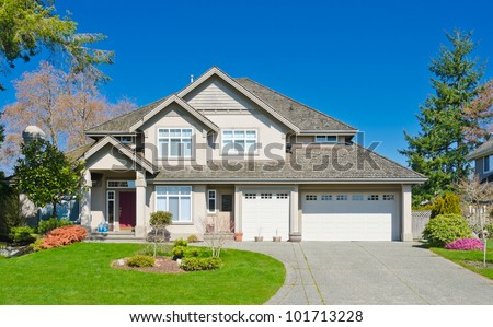 Luxury home with triple garage doors and the blue sky as a background in suburbs of Vancouver, Canada.