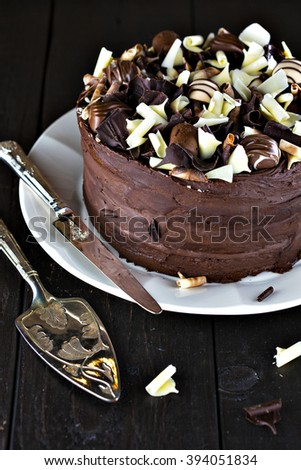 Luxury homemade chocolate cake with shovel and cutting knife on dark brown wooden table. - stock photo