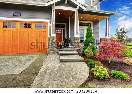 Luxury house entrance porch with stone column trim. View of  walkway with landscape - stock photo