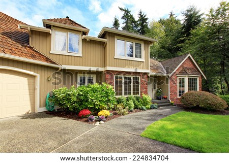 Luxury house exterior with brick trim, tile roof and french windows. Front yard landscape with lawn - stock photo