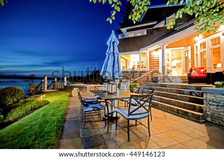luxury house exterior with impressive water view and cozy patio area summer evening - Luxury House Exterior