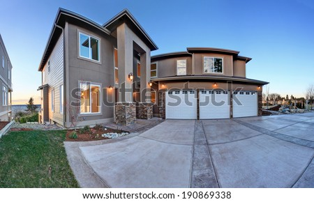 luxury house exterior with three car garage and driveway evening view