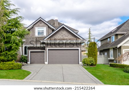 Luxury house with a two-car garage against blue sky. Exterior design. - stock photo