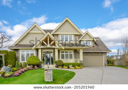 Luxury house with a two-car garage and beautiful landscaping on a sunny day. Home exterior. - stock photo