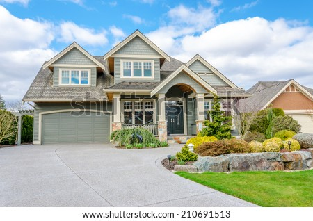 luxury house with a two car garage and beautiful landscaping on a sunny day