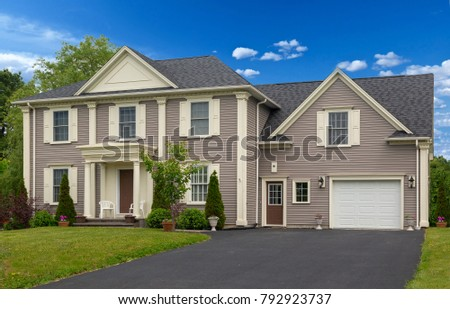 Luxury house with nicely trimmed and landscaped front yard, lawn in a  North American residential neighborhood.