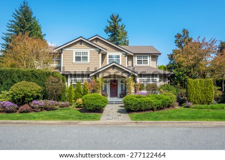 Luxury house with nicely trimmed front yard, lawn in a residential neighborhood. Home exterior. - stock photo