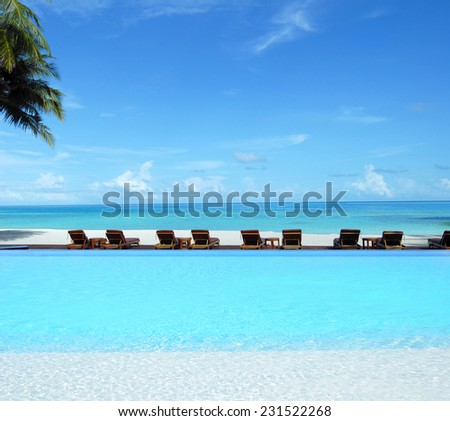 Luxury infinity swimming pool at tropical beach hotel  -- Tropical vacations concept  - stock photo