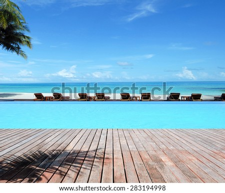 luxury infinity swimming pool at tropical beach -- Tropical beach vacation and travel concept - stock photo