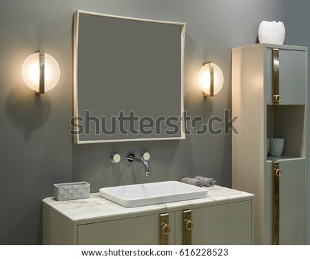 Luxury Interior bathroom: wall mounted mixer, inset washbasin, large mirror, electric lamps and furniture