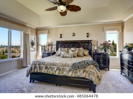 Luxury interior of master bedroom with black furniture. King size bed with headboard and tropical patterned bedding. Northwest, USA