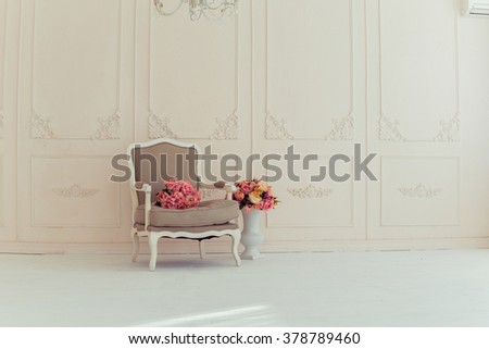 luxury interiors in beige tones. Elegant vintage armchair in a spacious room with a wall decorated with ornaments. colorful flowers in a vase standing on the wooden floor - stock photo