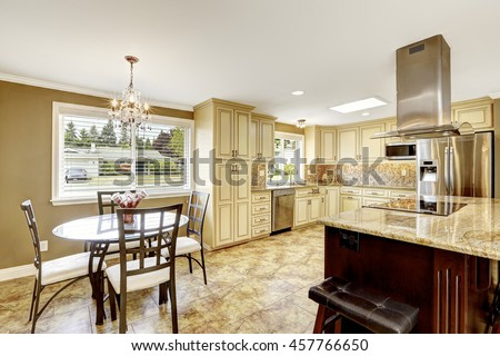 Luxury kitchen interior in light beige color with back splash trim and tile floor. Also dining area - stock photo