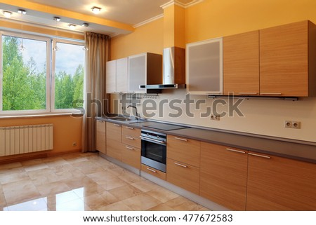 Luxury kitchen interior with orange walls , stone floor and forest view