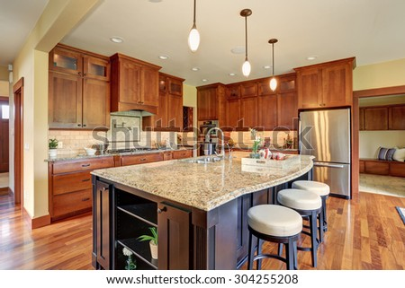 Luxury kitchen with bar style island, and hardwood floor. - stock photo