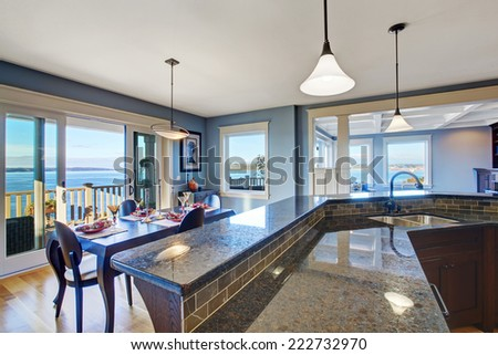 Luxury kitchen with dark brown cabinets and granite top. Kitchen has dining area and sliding doors to walkout deck - stock photo