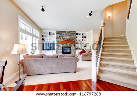 Luxury large beige living room with staircase and stone fireplace. - stock photo