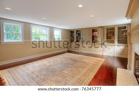 Luxury large room with cherry mahogany hardwood floor and custom made cabinets with entertainment center. Basement in a historical luxury home in Tacoma, WA - stock photo