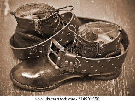 luxury leather shoes and a leather belt with buckle. cowboy style. vintage style. Photo toning in sepia - stock photo