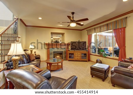 Luxury living room interior with fireplace and carpet floor. Black leather sofa and armchairs, orange curtains