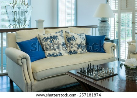 luxury living room with blue pattern pillows on sofa and decorative chess board   - stock photo