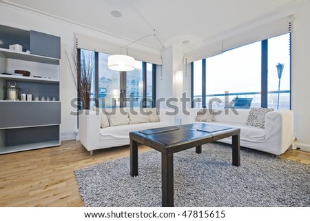 luxury living room with floor to ceiling windows and modern furniture - stock photo