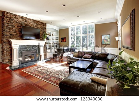 Luxury living room with stone fireplace and leather sofas, cherry hardwood and nice rug.