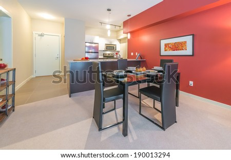 Luxury living suite : dining room with the nicely served table and red wall and the kitchen at the back . Interior design.