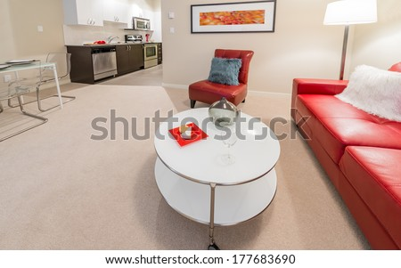 Luxury living suite of brand new house. Nicely decorated modern family, living room with red color couch, chair and coffee table and a kitchen site at the back. Interior design. - stock photo