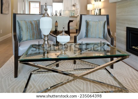 Luxury living suite: two modern chairs at the coffee table and the kitchen at the back. - stock photo