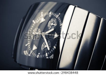 Luxury mens chronograph watch made of black high-tech ceramics lays on dark backdrop. Closeup studio photo with tonal filter and selective focus - stock photo