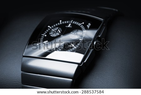 Luxury mens chronograph watch made of black high-tech ceramics lays on leather backdrop. Closeup studio photo with selective focus - stock photo