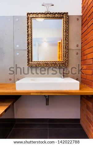 Luxury mirror and wash basin in a modern bathroom - stock photo