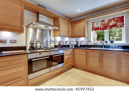Luxury modern fitted kitchen with stainless steel appliances, granite work surfaces and two ovens - stock photo