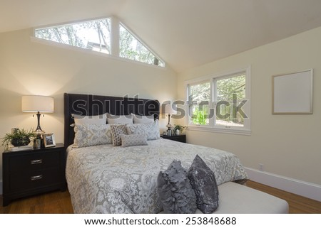 Luxury modern home bedroom with rug, view window and cherry wooden flooring with peaked roof with windows.  - stock photo