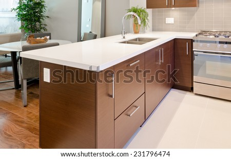 Luxury modern kitchen with dining table at the back. Interior design of a brand new house. - stock photo