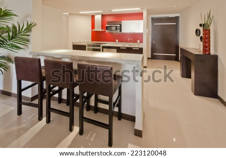 Luxury modern living suite with  nicely decorated dining table and red walls kitchen at the back. Interior design of a brand new house. - stock photo