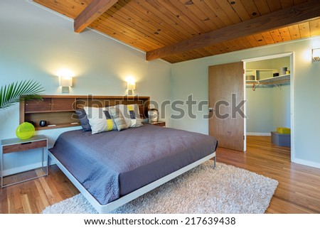 Luxury modern mid century home bedroom with decorated walk in closet and wooden ceiling. King size bed with hand-woven natural colored fine sisal runner, rug.  - stock photo