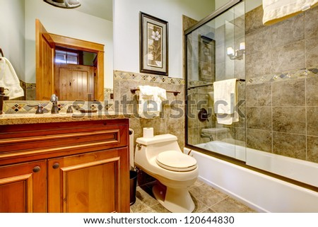 Luxury mountain home bathroom with shower, tub, natural stone tiles. - stock photo