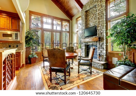 Luxury mountain home dining and living room with stone fireplace. - stock photo