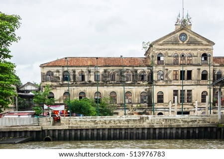 Luxury old mansions riverside Chao Phraya river on cloudy weather, Bangkok, Thailand. Image for travel inspiration, real estate agent business, realtor blog, architectural buildings.